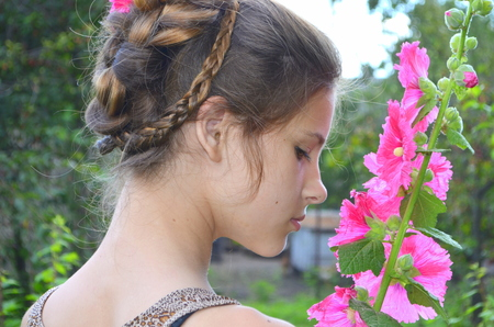 hollyhocks: Girl with hairstyle and pink hollyhocks Stock Photo