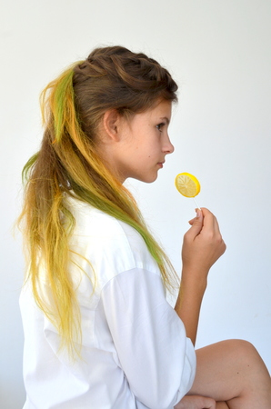 strands: Girl with colored strands and with a lollipop