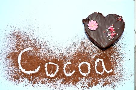 Torta bajo la forma de un corazón con el polvo de chocolate y el cacao