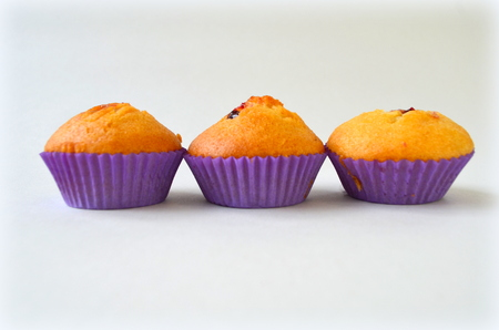 Muffin with black currant on white background