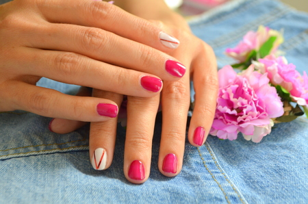 Manicure short red nails and white on the index finger