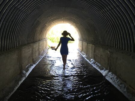 girl walking barefoot through the water in a dark tunnel to the light Zdjęcie Seryjne