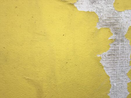 an old yellow wall with a peeling area and plastic mesh inside 스톡 콘텐츠