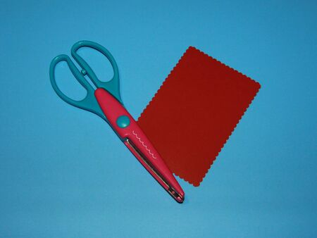 curly scissors for cutting paper and red cardboard cut in the shape of a rectangle Stok Fotoğraf