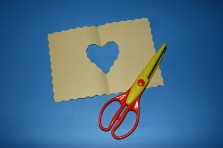 scrapbooking scissors, big wave pattern, colored paper cut out a heart shaped hole