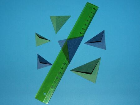 transparent plastic ruler and green and blue triangles cut out of colored paper
