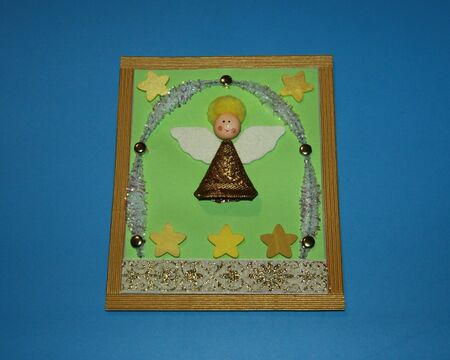 greeting card angel made of wooden head and fleece wings in golden clothes with ornament and chenille Zdjęcie Seryjne