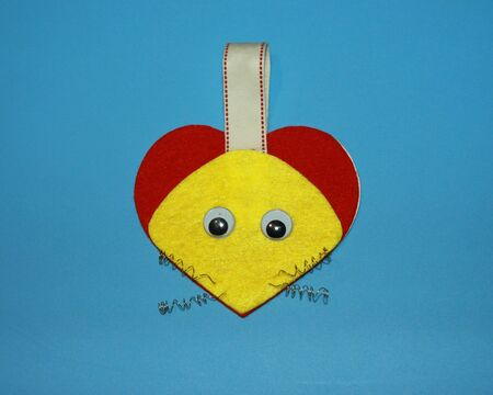 Greeting card Valentine mouse in red and yellow colors and in the shape of a heart and with a spring mustache