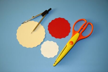 compasses, yellow scissors for scrapbooking, big wave pattern, three circles of red, cream and white colors are cut out of colored paper Stok Fotoğraf - 129825997