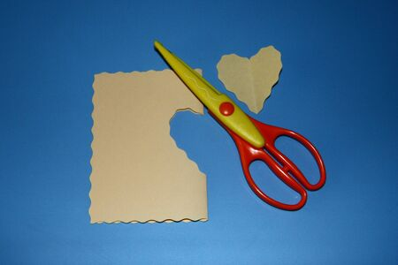 scrapbooking scissors, big wave pattern, colored paper cut in the shape of a heart Stok Fotoğraf