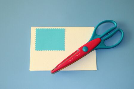 scrapbooking scissors, wave pattern, colored paper blue cut out rectangle for greeting card Stok Fotoğraf
