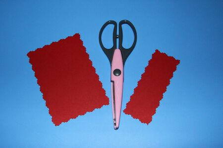 pink scissors for scrapbooking, decorative filigree pattern, two rectangles of red color are cut out of colored paper