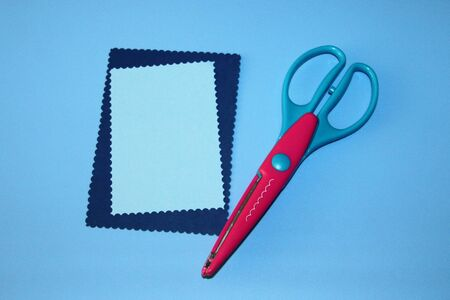 red scrapbooking scissors, cloud pattern, two rectangles cut out of paper