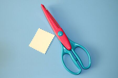 curly scrapbooking scissors for paper cutting and pastel cardboard cut in the shape of a rectangle