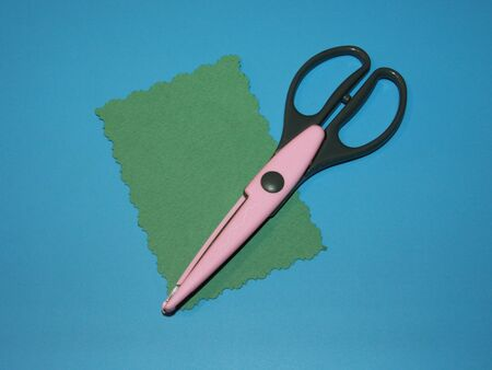 pink scissors for scrapbooking curly for paper cutting and green cardboard cut in the shape of a rectangle Stok Fotoğraf