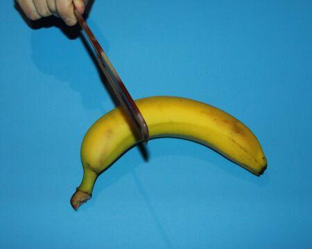 fingers hold a comb over a ripe yellow banana Banco de Imagens - 133077743