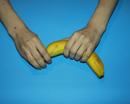 female hands hold a ripe yellow banana and open Banco de Imagens - 133078452