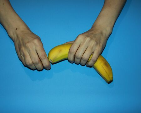 female hands hold a ripe yellow banana and open Banco de Imagens - 133077853