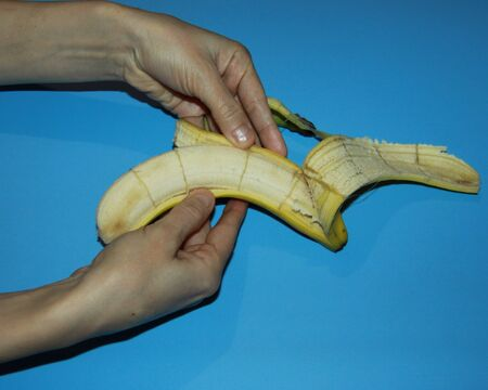 female hands hold a ripe yellow banana and open Banco de Imagens - 133077737
