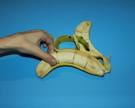 female hands peel a banana and hold sliced pieces with their fingers Banco de Imagens - 133078158