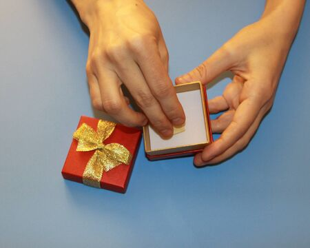 Valentines Day hands holding a red gift box with a gold shiny bow and a paper note sheet 版權商用圖片