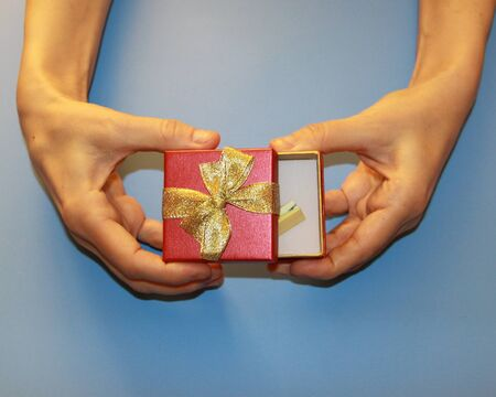valentines day hands hold red gift box with golden shiny bow surprise