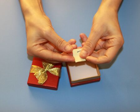 Valentines Day hands holding a red gift box with a golden shiny bow in which a note a declaration of love, surprise