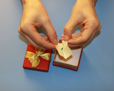 hands holding a red gift box with a gold shiny bow in which the note is the number one