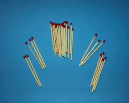 pile of wooden matches with a red tip head lie on a blue background