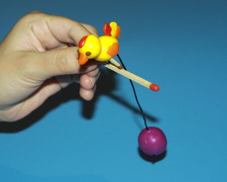 puzzle experiment hand holds a wooden match on which stands a bird molded of plasticine with a metal wire inserted into it for balance