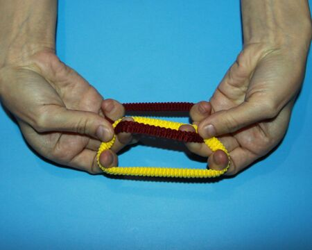 magician shows how brown and yellow rubber for hair passes through fingers a magic trick