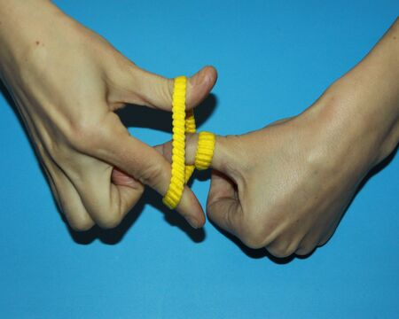 magician shows how yellow rubber for hair passes through fingers a magic trick