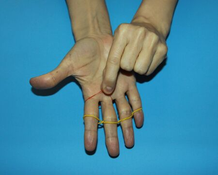 magician shows how red and yellow clerical rubber passes through fingers a magic trick
