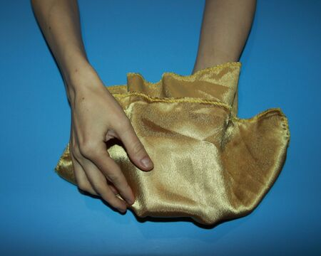 illusionist magician hand holds gold satin shawl demonstrate gift disappearance 写真素材