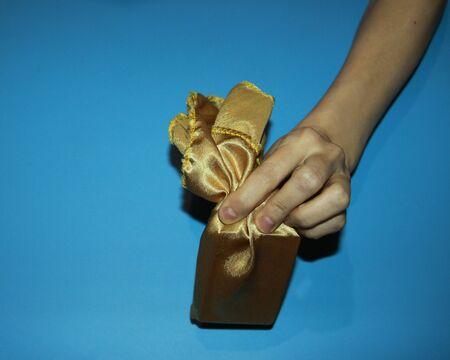 illusionist magicians hand holds a golden satin shawl demonstrate the disappearance and appearance of a gift
