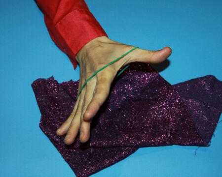 magician the illusionist holds rubber and a handkerchief in purple and shows a magic trick