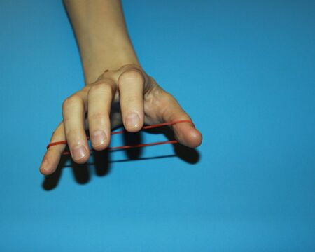 magician shows how red clerical rubber passes through fingers a magic trick Imagens