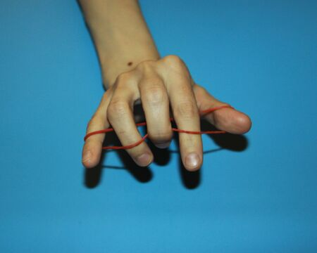 magician shows how red clerical rubber passes through fingers a magic trick Stock fotó