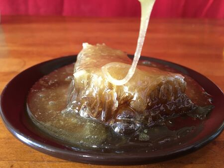 ecological pouring honey honeycombs in a clay brown plate on a wooden background 写真素材