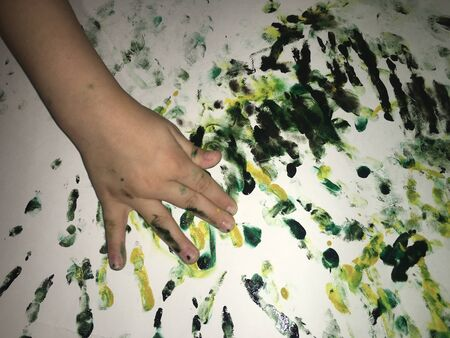 childrens hands stained with paint and fingers paint an abstract pattern with watercolors