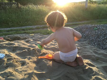 baby in the diaper plays with the sand, the sun shine over his head
