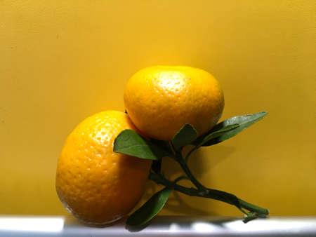 ripe tangerine with green leaves Фото со стока