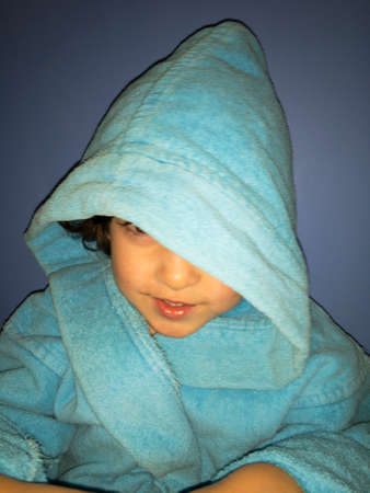 a boy in a bathrobe after a bath looks out from under the hood