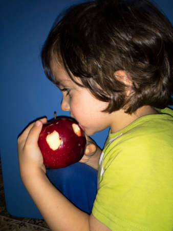 a small child with appetite took a bite and eats with pleasure a fresh juicy red apple Фото со стока