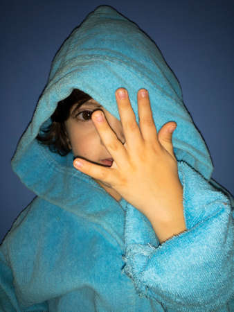 handsome boy in a robe in a hood shows the number five on his fingers Фото со стока