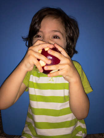 child holding a ripe red apple and eating Фото со стока