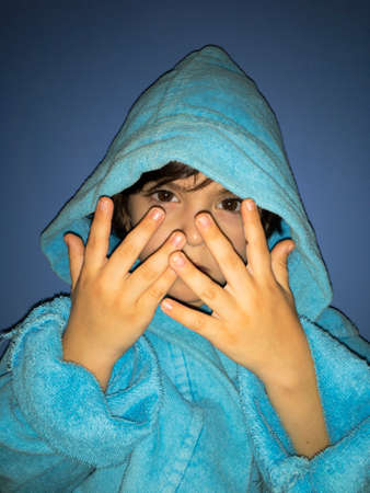 handsome boy in a robe in a hood looks strictly covers his face with his hands Фото со стока