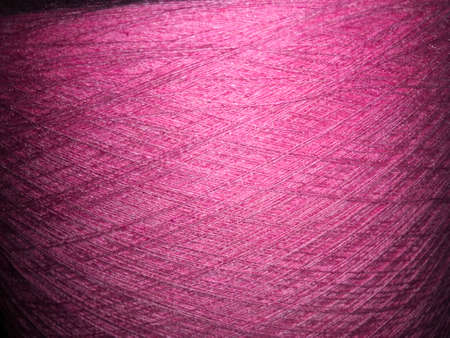 background of pink threads for knitting, large bobbins