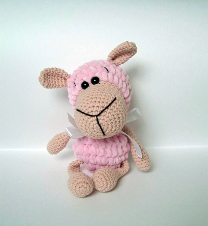 Crochet doll. A handmade crochet doll of a little lamb in pink Banque d'images - 109944412