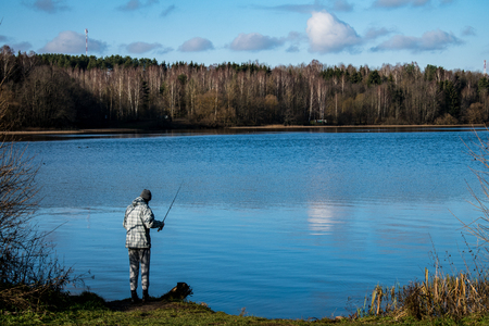Man fishing with a fishing rod on the shore of the pond in Sunny weather